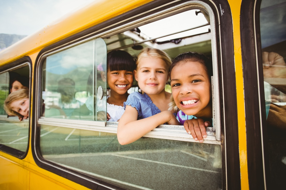 Cute pupils smiling at camera in the school bus outside the elementary school.jpeg