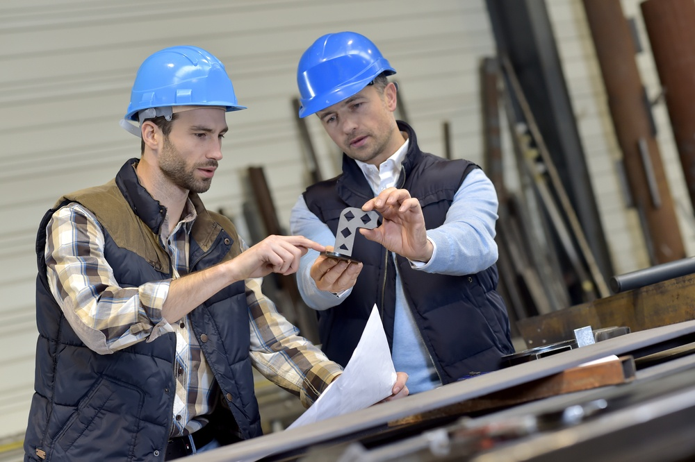 Engineer with mechanical worker checking on production.jpeg