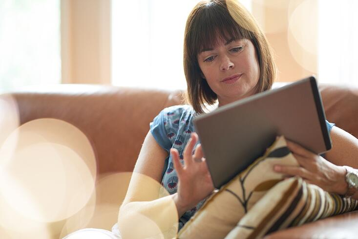 Mature woman browsing the internet on a digital tablet.jpeg