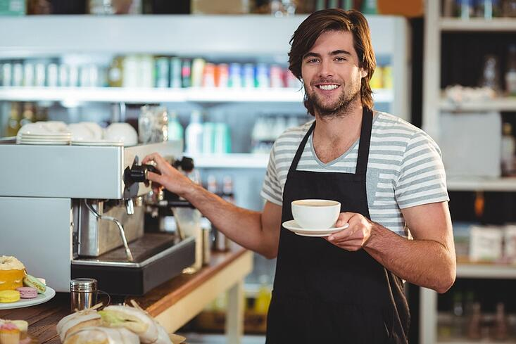 Portrait of smiling waiter holding cup of coffee in cafe.jpeg