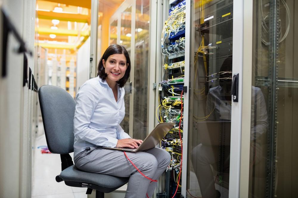 Portrait of technician working on laptop in server room.jpeg
