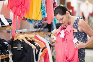 Woman looking at pink shirt in clothes store